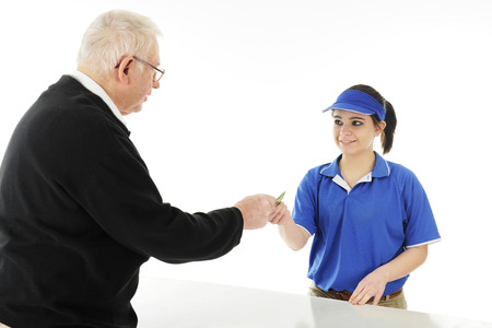 over the counter: A senior man customer reaches over a counter to pay a young employee.  On a white background.
