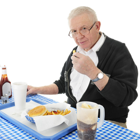 bifocals: A senior adult man looking up at the viewer as he enjoys a french fry from his fast food basket.  On a white background.