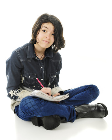 looking at viewer: A pretty young teen happily looking at the viewer while sitting cross legged on the floor with pencil and note pad.  On a white background. Stock Photo