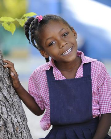 A happy Haitian elementary girl sitting in a tree in her school uniform. Stock Photo