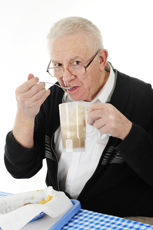 bifocals: A senior adult man peering over his glasses as he eats icecream from his rootbeer float.  A basket of half-eaten french fries are on the table before him.  On a white background.
