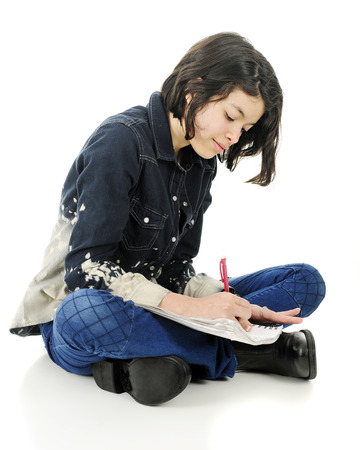 An attractive young teen happily sitting cross-legged on the floor while writing in her note pad.  On a white background.