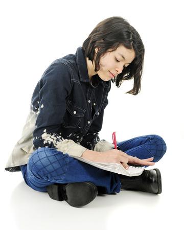 persona escribiendo: Una atractiva joven adolescente feliz sentado con las piernas cruzadas en el suelo mientras escribe en su cuaderno de notas. Sobre un fondo blanco.