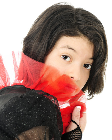 looking at viewer: A shy young teen looking out at the viewer from being sheer red frills.  On a white background.