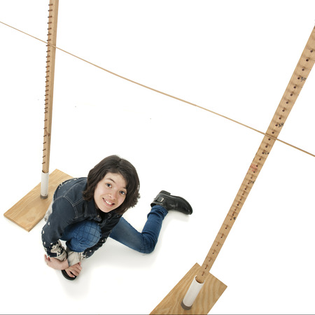 limbo: An overhead view of a young teen girl who has fallen under a limbo stick.  On a white background.
