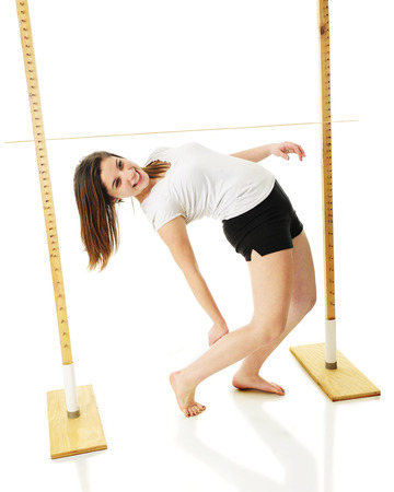 white backing: An attractive teen girl successfully backing under the limbo stick.  On a white background. Stock Photo