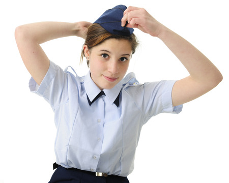 navy blue background: An attractive teen girl putting on her navy blue  uniform hat.  On a white background. Stock Photo