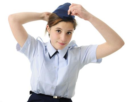 azul marino: Una chica atractiva adolescente que pone en su sombrero de color azul marino uniforme. Sobre un fondo blanco.