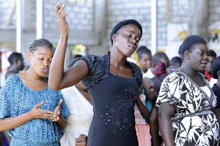 Unidentified Haïtiaanse vrouwen aanbidden in een kerk bij Bois Neus, Haïti. Focus op center vrouw met haar ogen dicht en met de hand opgevoed.