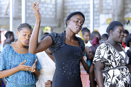 Unidentified Haitian women worshipping in a church at Bois Neus, Haiti.  Focus on center woman with her eyes closed and hand raised.