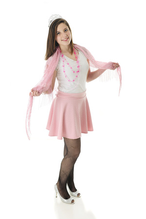 lacey: A beautiful teen princess happily posing in the silver crown and shoes, and pink skirt, lacey shawl and necklace of hearts.  On a white background.