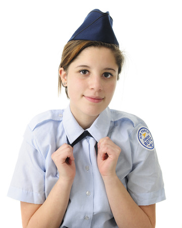 auburn hair: Closeup of a pretty teen girl straightening the tie of her Jr. ROTC uniform.  On a white background. Stock Photo