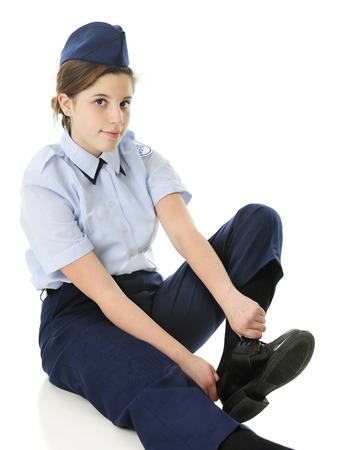 putting on: An attractive teen girl in her Jr. ROTC uniform, putting on her shoes.  On a white background.