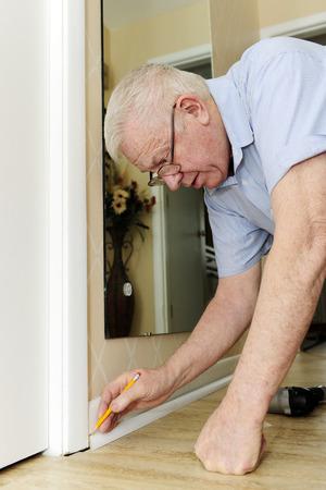 A senior adult man measuring the baseboard quarter round for proper installation.