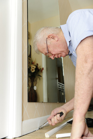 baseboard: A senior man pulling nails from his baseboard as he upgrades his home. Stock Photo