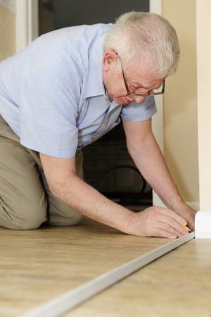 refurbishing: A senior adult man measuring new quarter round to replace the old on his baseboards. Archivio Fotografico