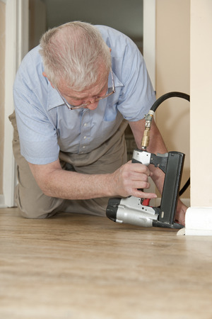 compressed air hose: A senior man on his hands and knees, using an air-compressed stapler to attach new quarter round to his baseboards.  Space on bottom (home floor) for your text.