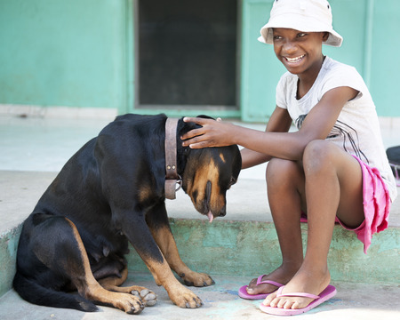 tween: A tween Haitian girl happily petting a large black dog.