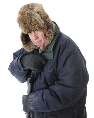 grouch: Close-up of a bundled senior man, grumpy as he leans on the handle of he snow shovel.  On a white background.