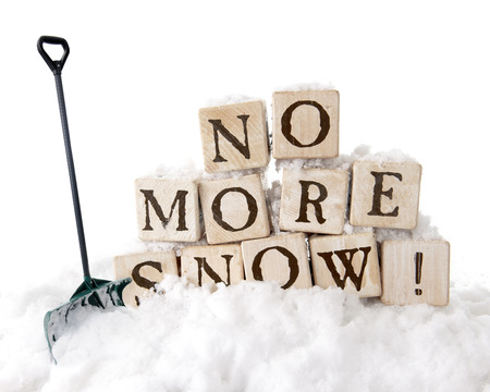 no snow: Large, rustic alphabet blocks arranged to say, No More Snow! surrounded by snow with a snow shovel nearby Isolated on white. Stock Photo
