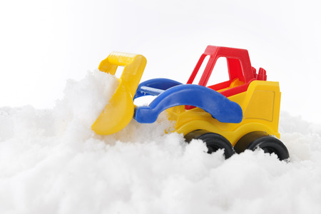 A colorful plastic front loader scooping real snow Stock Photo