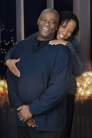 mature male: A happy and attractive, mature African American couple before nighttime windows and white Christmas lights.
