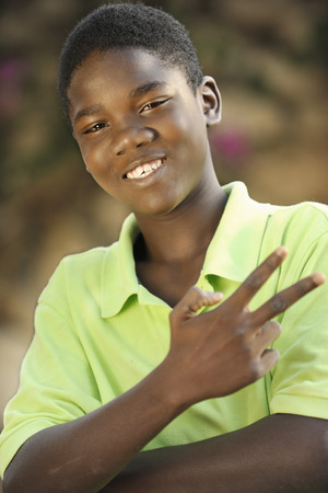 haitian: Close-up image of a happy young Haitian teen boy gesturing victory with his fingers.  Shallow DOF with focus on eyes.
