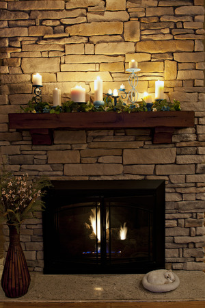 A sleeping kitty by a cozy fireplace.  The mantle is decorated with a variety of lit candles which give the stone chimney a golden glow.