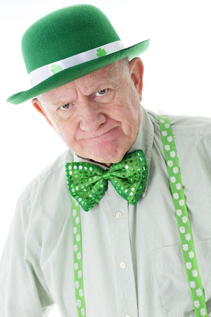 Closeup image of a grumpy senior man dressed all in green.  His suspenders and hat are adorned with shamrocks.  On a white background. Stock Photo