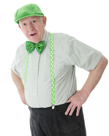 A surprised senior adult man looking happily surprised in his green hat, tie and shamrock-adorned suspenders.  On a white background.