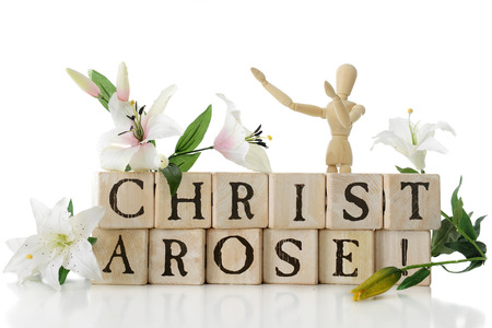 glorify: Alphabet blocks arranged to say, Christ Arose! surrounded by Easter lillies and a wooden mannequin with arms upraised in praise.  Isolated on white.