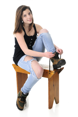 work boots: A beautiful teen girl looking at the viewer as she puts on her work boots.  On a white background. Stock Photo