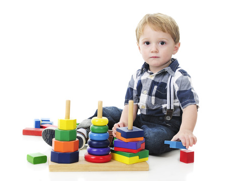 he: An adorable toddler looking at the viewer as if to ask, Am I doing it right? as he plays with a stack toy.  On a white background.