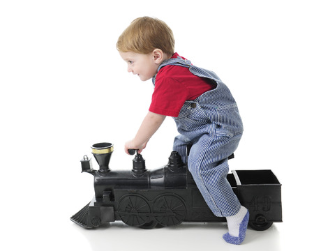 Sied view of an adorable 2-year-old train engineer scooting along on a toy train engine.  On a white background.