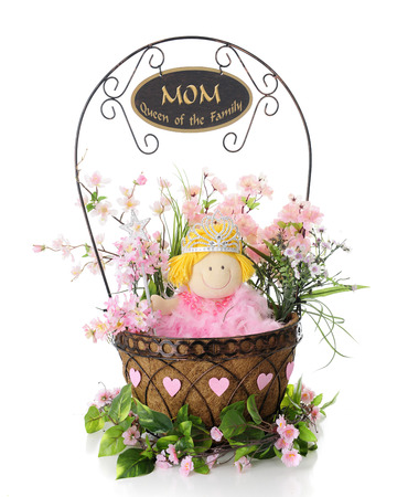 queen of hearts: A wire basket filled with a doll dressed as a queen among green and pink foliage.  Hearts surround the basket and a sign on the handle reads, MOM, Queen of the Family.  On a white background.
