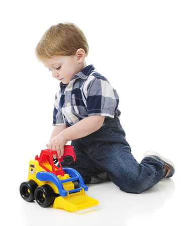 front loader: An adorable 2-year-old playing on the floor with a toy front loader.  On a white background.