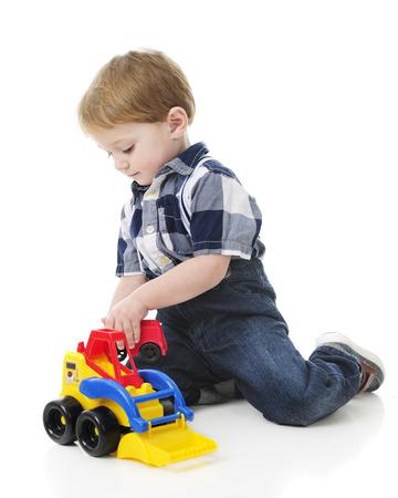 front loader: Un juego de 2 a�os de edad adorable en el suelo con un cargador frontal juguete. Sobre un fondo blanco. Foto de archivo