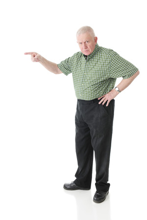 A senior man glaring at the viewer while pointing to the right.  On a white background. Imagens