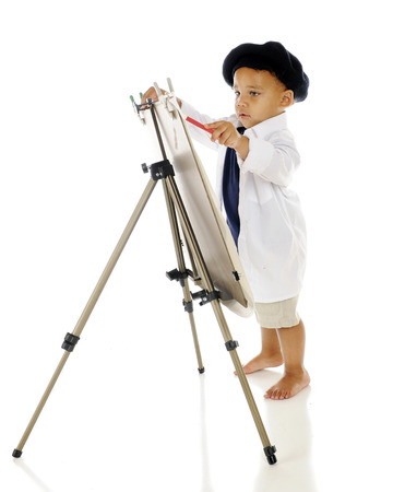 children painting: An adorable preschooler concentrating as he paints on an easel in his smock and French beret.  On a white background. Stock Photo