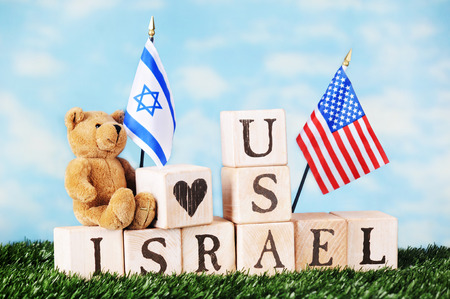 david brown: A toy bear sitting on alphabet blocks arranged on a bed of grass to say Israel and USA.  A heart shape and an  American and Israeli flag fly over them.  All against a lightly clouded sky. Stock Photo
