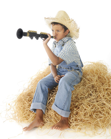 An adorable young farm boy in blue denim overalls, blowing a born as he sits barefoot on a haystack.  On a white background. 免版税图像