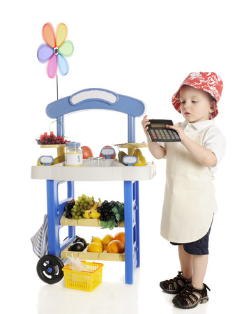 figuring: An adorable preschooler standing by his fruit stand while calculating his profits to show the viewer.  The stands signs are left blank for your text.  On a white background.