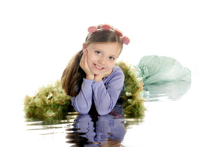 watery: A beautiful young elementary mermaid laying on a watery reflection.  On a white background.