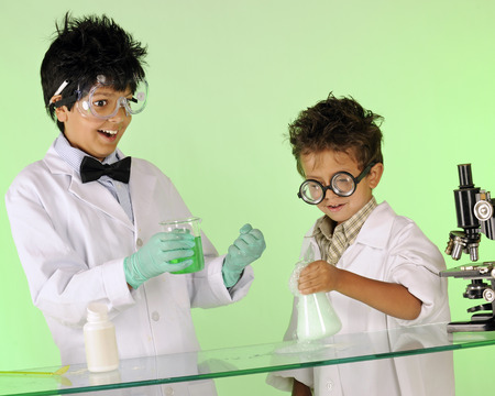 wild hair: Two mad scientist brothers, with wild hair and protective clothes, displaying success as they combine chemicals.