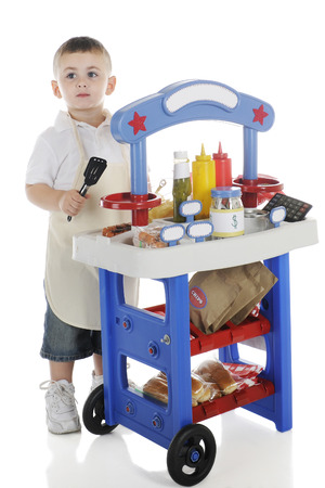 a jar stand: A young preschooler tending his hot dog stand.  The stands signs are left blank for your text.  On a white background.