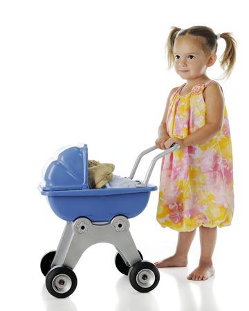 """niño empujando: Una bonita niño en edad preescolar, descalzo empujando su muñeca de trapo """"bebé"""" en un cochecito de muñecas. En un bckground blanco."""