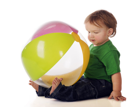 beachball: An adorable baby boy holding a large, colorful beachballs, with his feet.  Isolated on white.
