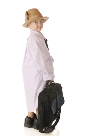 handome: A handsome kindergarner looking back as he carries a computer case while dressed in grandpa