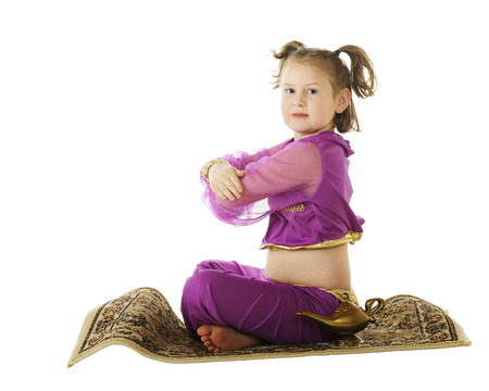 A young elementary genie coming in for a landing on her flying carpet.  Isolated on white, photo