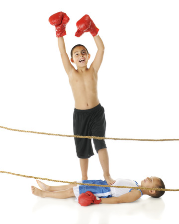 exclaiming: An elementary-aged boxer (with a black eye) exclaiming victory orver his happy preschool brother who lays out flat under the victor Stock Photo